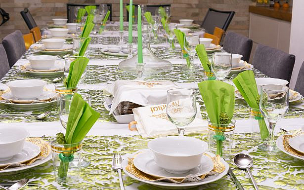 "Modern Passover Seder table with green  and gold decorations in Tel Aviv, Israel, complete with Matzos and a traditional Seder Plate.  Matzo covers read ""Matzo"" and ""Afikoman"" in Hebrew."