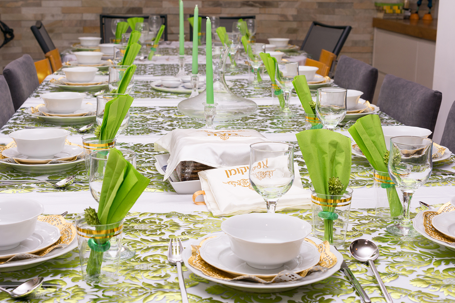 """Modern Passover Seder table with green  and gold decorations in Tel Aviv, Israel, complete with Matzos and a traditional Seder Plate.  Matzo covers read """"Matzo"""" and """"Afikoman"""" in Hebrew."""
