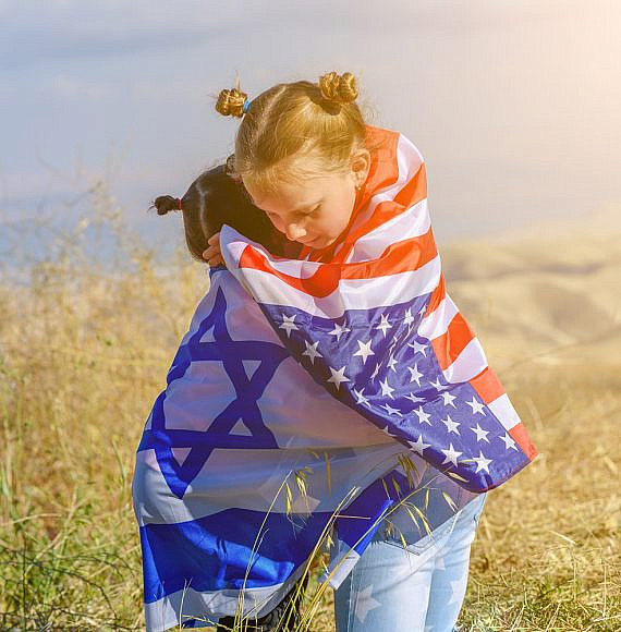 Two cute girls with American and Israel flags. Little children holding Israeli and USA flags hugging on meadow with beautiful landscape in background.Two nations one heart concept.