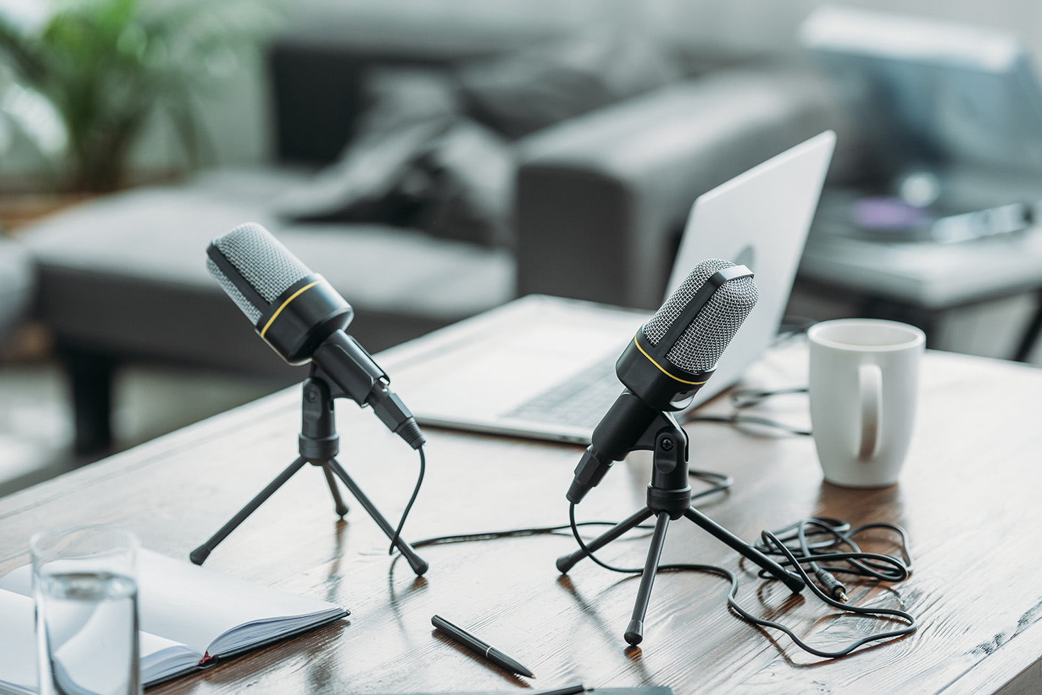two microphones, laptop, notebook and coffee cup on wooden table in radio studio